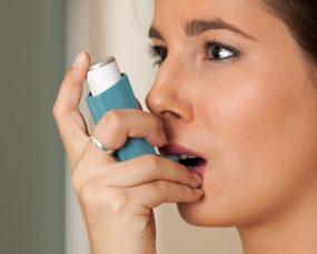 women using asthma inhaler